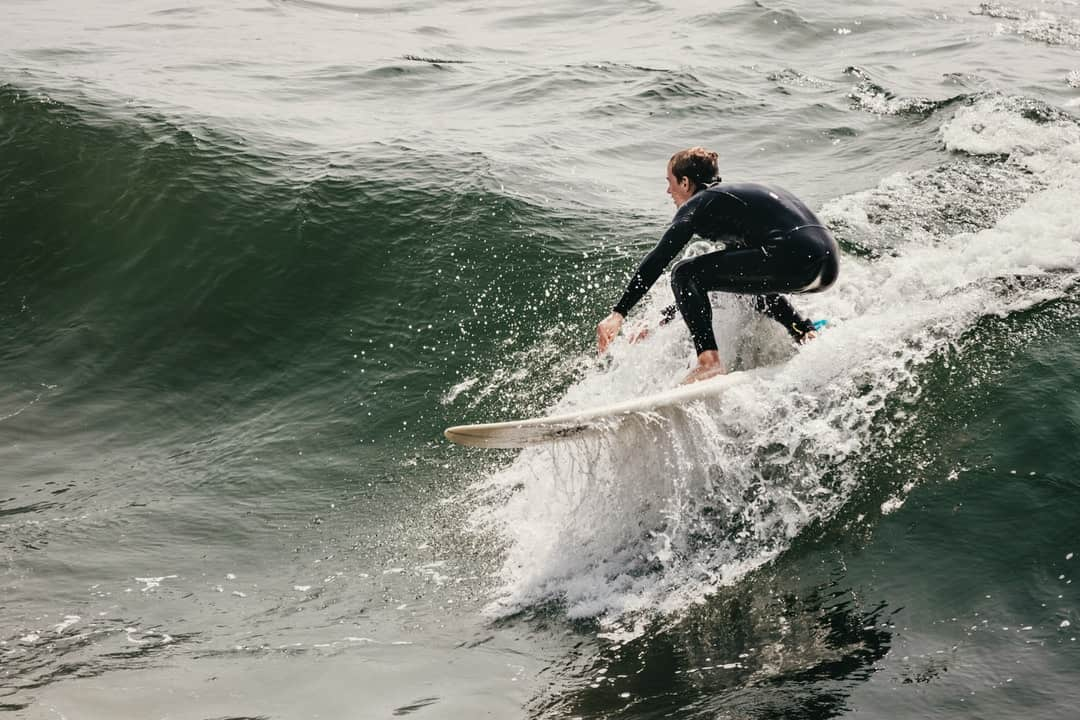 A person wearing a wet suit riding a wave in the ocean